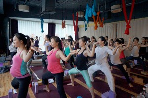 Students wear a fake belly and practice the moon salutation.